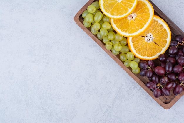 Uvas e fatias de laranja na placa de madeira.