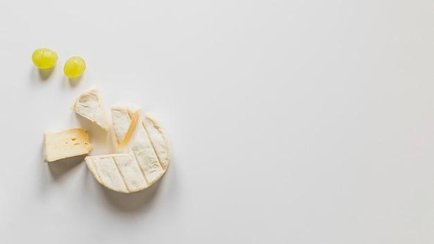 Uvas e queijo blocos isolados no fundo branco