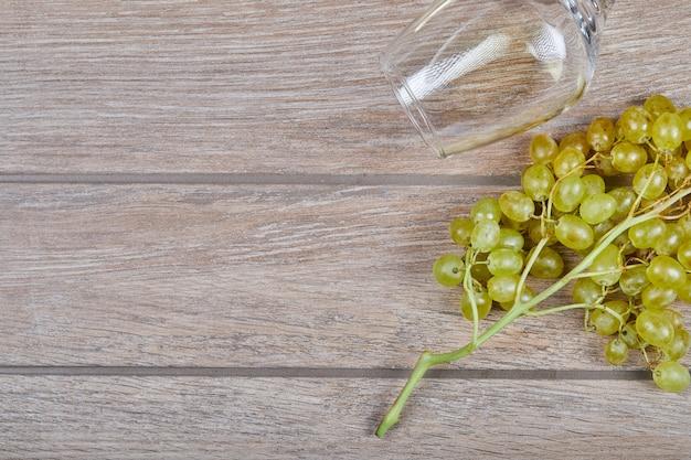 Uvas e taça de vinho na superfície de madeira