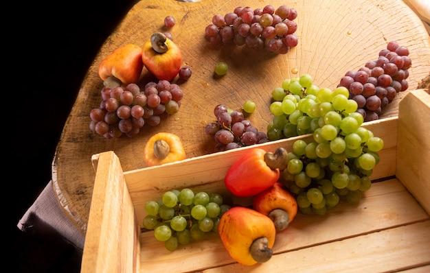 Uvas em caixa de madeira e cajus com tecidos ao fundo, baixa profundidade de campo