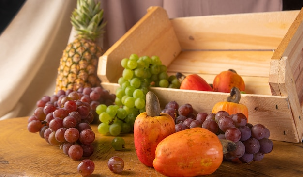 Uvas em caixinha de madeira e cajus e abacaxi com tecidos ao fundo e madeira rústica, baixa profundidade de campo