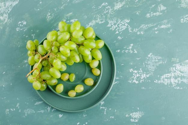 Uvas em pires e placa plana sobre um fundo de gesso