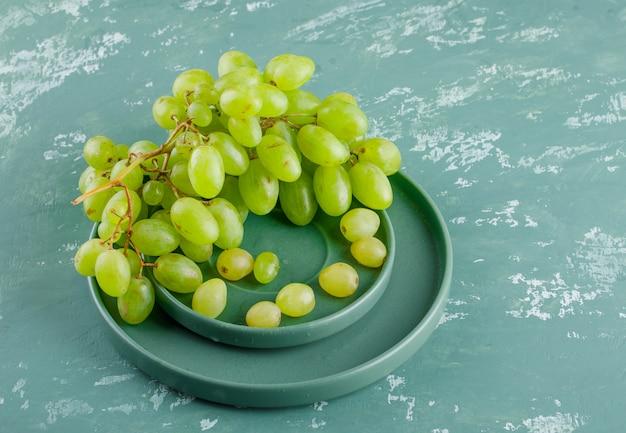 Uvas em pires e placa sobre um fundo de gesso. vista de alto ângulo.