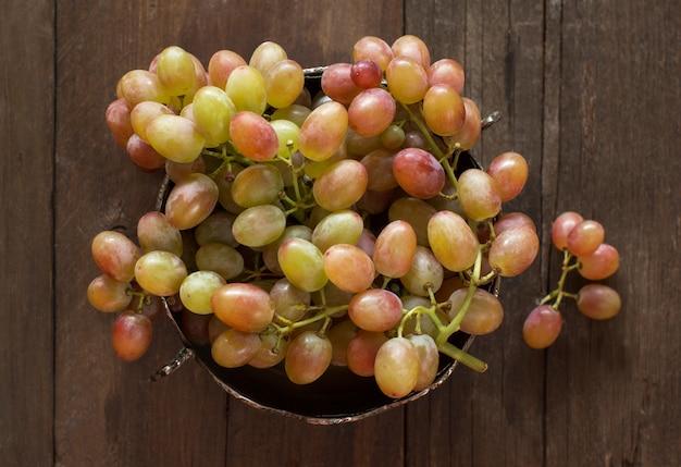 Uvas em tigela de prata vista superior na mesa de madeira