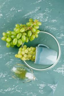 Uvas em um copo com vista superior da bebida no fundo de gesso e bandeja