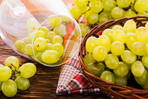 Uvas em um copo de vinho e uma cesta de uvas em cima da mesa