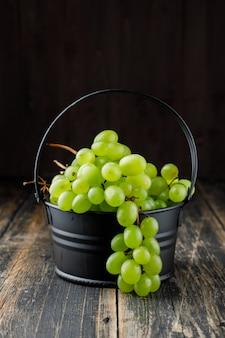 Uvas em um mini balde vista lateral em uma superfície de madeira
