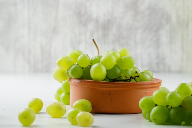 Uvas em um prato de barro na superfície branca, vista lateral.