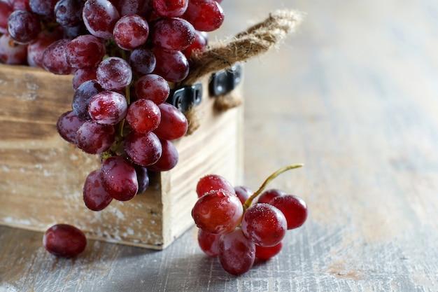 Uvas em uma caixa de madeira em uma velha mesa de madeira