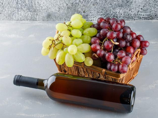 Uvas em uma cesta com vista de alto ângulo da garrafa de bebida em gesso e suja