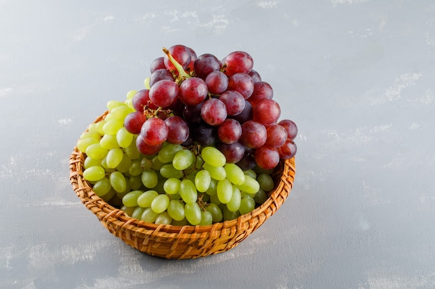 Uvas em uma cesta de vime, vista de alto ângulo em um gesso cinza