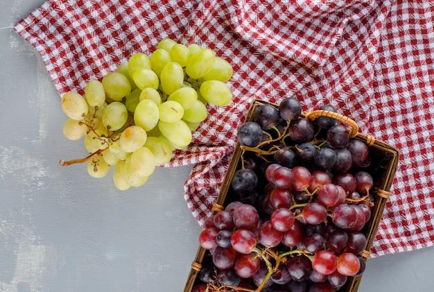 Uvas em uma cesta em gesso e pano de piquenique.