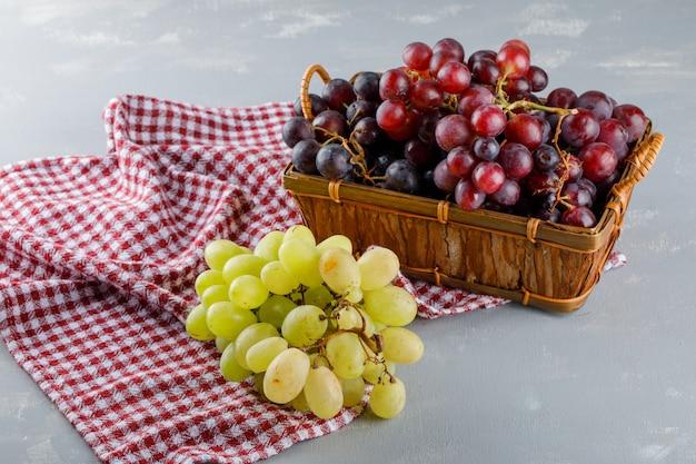 Uvas em uma cesta em pano de piquenique e gesso, vista de alto ângulo.
