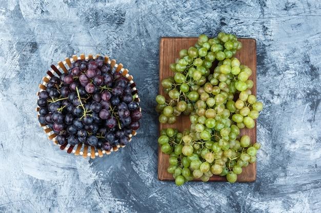 Uvas em uma cesta plana colocadas sobre gesso sujo e fundo de tábua de corte