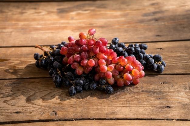 Uvas em uma mesa de madeira ramo fresco de uvas vermelhas com folhas