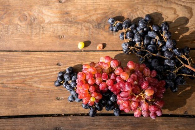 Uvas em uma mesa de madeira ramo fresco de uvas vermelhas com folhas Foto Premium