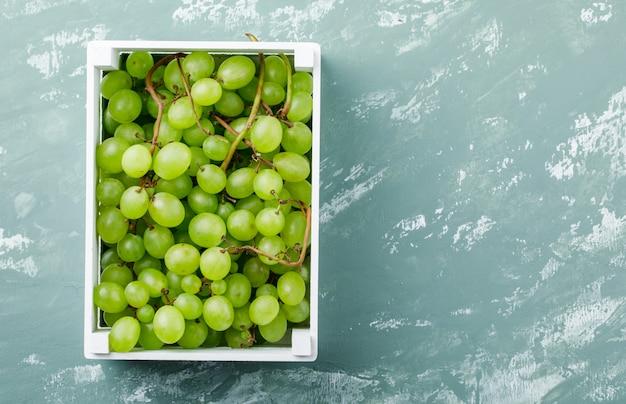 Uvas em uma vista superior da caixa de madeira em um fundo de gesso sujo