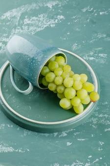 Uvas em uma xícara no fundo de gesso e bandeja. vista de alto ângulo.