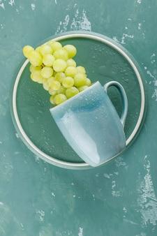 Uvas em uma xícara, vista superior sobre gesso e fundo da bandeja