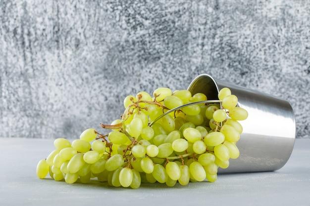 Uvas espalhadas de um mini balde em gesso e sujo.