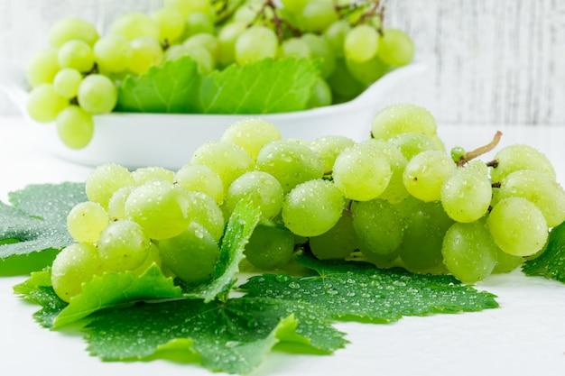 Uvas frescas com folhas em um prato na superfície branca