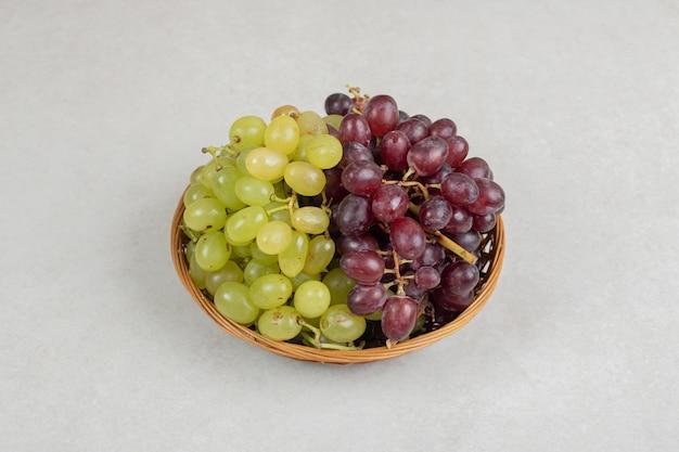 Uvas frescas de vermelhas e verdes em uma cesta de madeira.