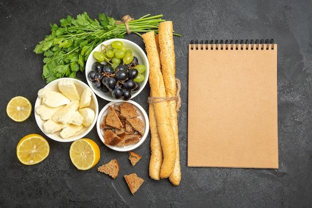 Uvas frescas de vista de cima com folhas de queijo branco e pão escuro fatiado na superfície escura prato de café da manhã com leite e frutas