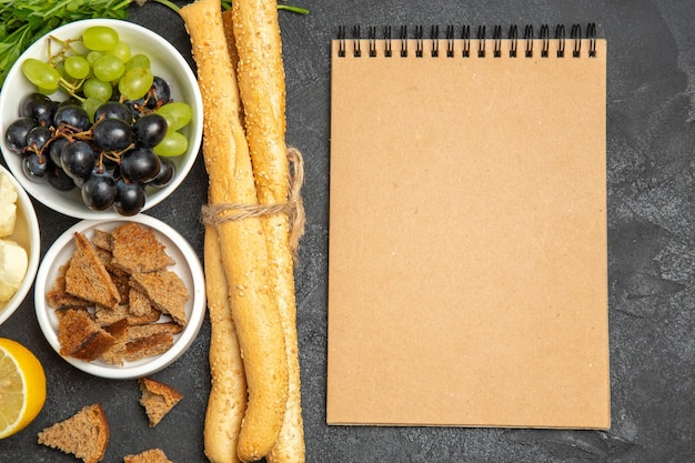Uvas frescas de vista superior com folhas de queijo branco e pão escuro fatiado na superfície escura refeição prato café da manhã frutas com leite