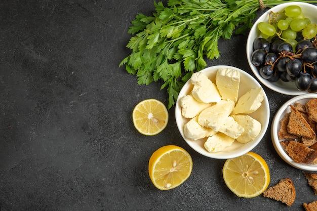 Uvas frescas de vista superior com folhas de queijo branco e rodelas de limão na superfície escura prato de café da manhã com leite e frutas