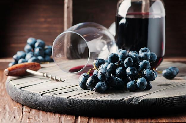 Uvas frescas e vinho tinto na mesa de madeira