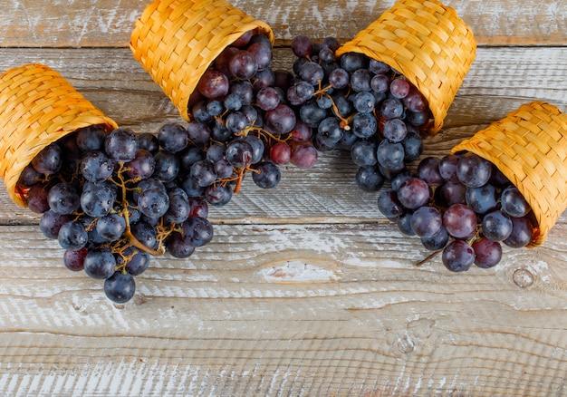 Uvas frescas em cestos de vime em um fundo de madeira. colocação plana.