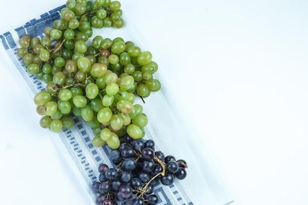 Uvas frescas em fundo branco e toalha de cozinha. colocação plana.
