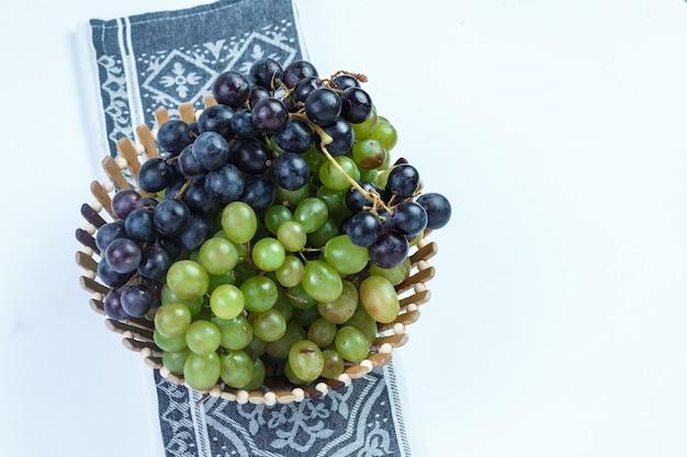 Uvas frescas em uma cesta em fundo branco e toalha de cozinha. vista de alto ângulo.