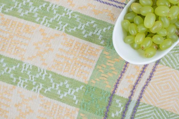 Uvas frescas em uma tigela branca na toalha de mesa.