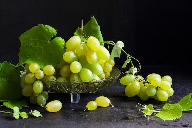 Uvas frescas maduras com folhas em uma fruteira de vidro em fundo preto