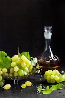 Uvas frescas maduras em uma fruteira e decantador com suco de uva em fundo preto