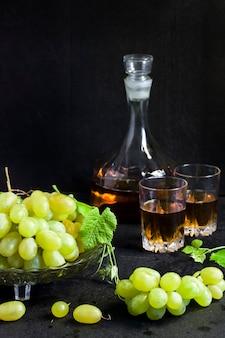 Uvas frescas maduras em uma fruteira e decantador e dois copos com suco de uva no fundo preto