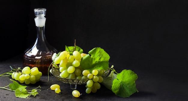 Uvas frescas maduras em uma fruteira e garrafa com suco de uva em fundo preto. copie o espaço