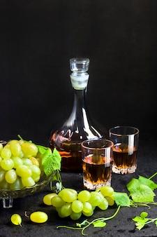 Uvas frescas maduras em uma fruteira, garrafa e dois copos com suco de uva em fundo preto