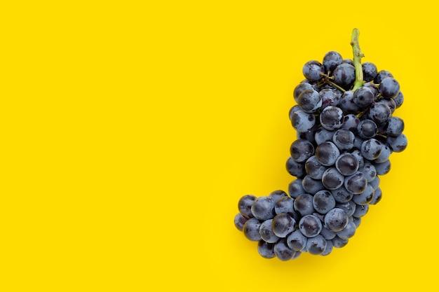 Uvas frescas pretas sobre fundo amarelo.