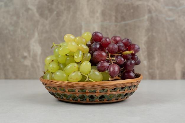 Uvas frescas vermelhas e verdes em uma cesta de madeira