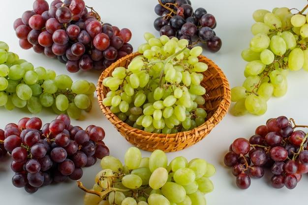 Uvas maduras em uma cesta de vime vista de alto ângulo em um branco