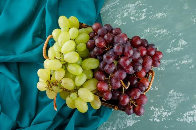 Uvas maduras em uma cesta plana sobre gesso e tecido