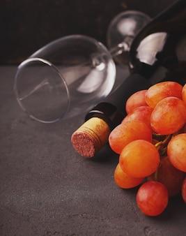 Uvas maduras, vinho tinto e um copo em um fundo preto