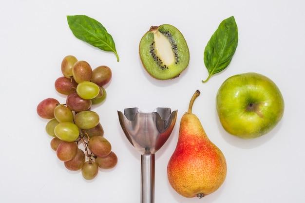 Uvas; manjericão; kiwi; maçã e pêra com liquidificador de mão elétrico no fundo branco