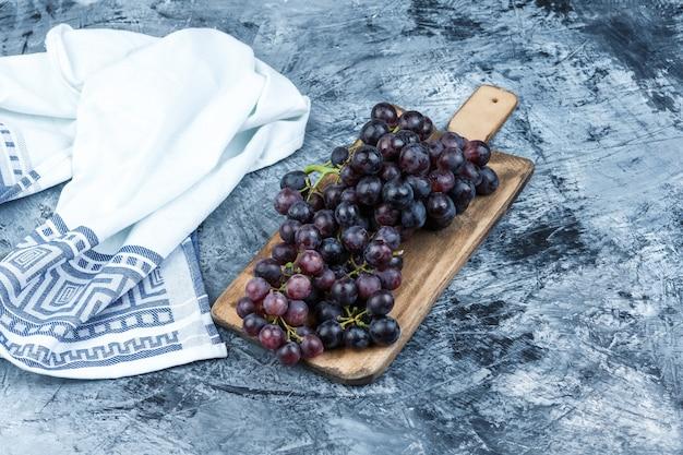 Uvas pretas com tábua de cortar em gesso sujo e fundo de toalha de cozinha, vista de alto ângulo.