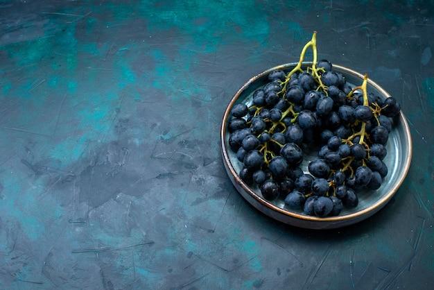 Uvas pretas de vista frontal dentro da bandeja em uma mesa azul-escura