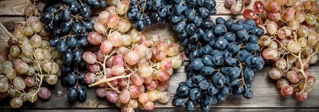 Uvas pretas e brancas. em uma mesa de madeira