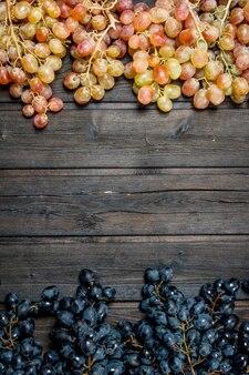 Uvas pretas e brancas. sobre um fundo de madeira.