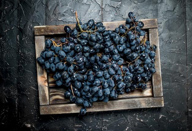 Uvas pretas em uma bandeja de madeira. sobre fundo preto rústico.